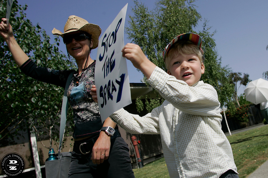 "Mill Valley, Calif. residents Pam Stone and her son Brewer, 5, hold signs during a march sponsored by the ""Mothers of Marin Against The Spray"" from Corte Madera Town Center to the town park to protest against the state of California's proposed pesticide spraying in Marin and the Bay Area to combat the light brown apple moth on Saturday, May 10, 2008.  The moth could possibly threated the states agriculture industry.  Parents are worried that the spraying will have severe health effects for their children."