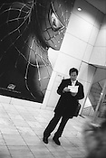 Man reading letter in front of Spiderman, Tokyo, Japan. 2004.