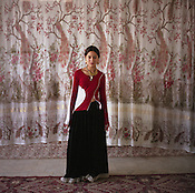 A Roma girl stands in front of a curtain on a wall bearing a design of peacocks, in a new house in the new part of Sintesti Roma camp..