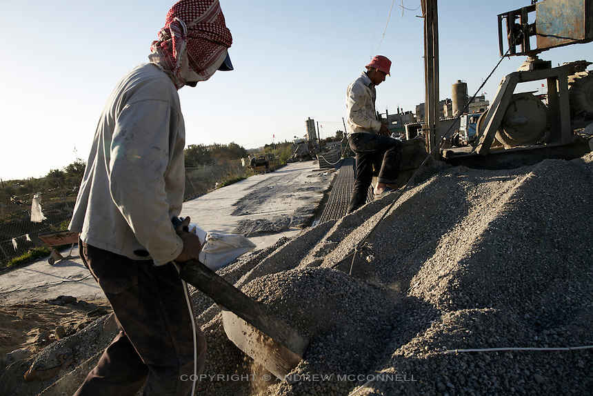 Men feed gravel into a mixer at a block factory in Beit Hanoun, Gaza. With more cement entering Gaza through the tunnels from Egypt there is a huge demand for aggregates for use in making concrete.