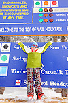 Girl in green parka, blue hat,and plaid pants plays in ski boots at trail sign on summit of Vail mountain.