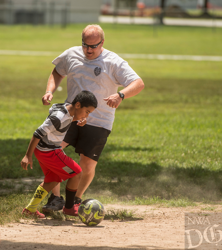 NWA Democrat-Gazette/ANTHONY REYES &bull; @NWATONYR<br /> Colton Brind, 9, tries to get past Travis Beyer, with the Springdale police department, Wednesday June 24, 2015 during a soccer game at Jones Elementary School in Springdale. Beyet and other officers were there as part of the Sandlot Program where they help mentor the students through play. The officers open up the gymnasium to the children who play and can eat lunch at the school free of charge.