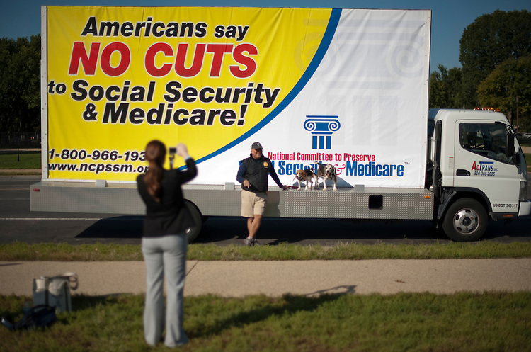 UNITED STATES - OCTOBER 6: Cal Kyriaki, of Falls Church, Va., poses with his beagles Zsa Zsa and Babalu in front of the National Committee to Preserve Social Security & Medicare's No Cuts campaign advertising truck parked on 3rd Street on the west side of the Capitol on Thursday, Oct. 6, 2011. (Photo By Bill Clark/CQ Roll Call)