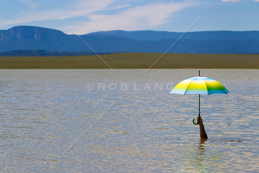 man underwater in a lake holding an umbrella over water