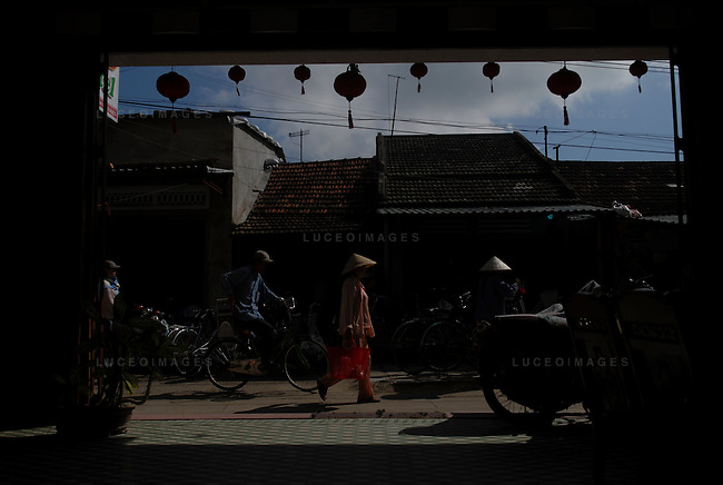 Vietnamese people walk in the streets of Hoi An, Vietnam.