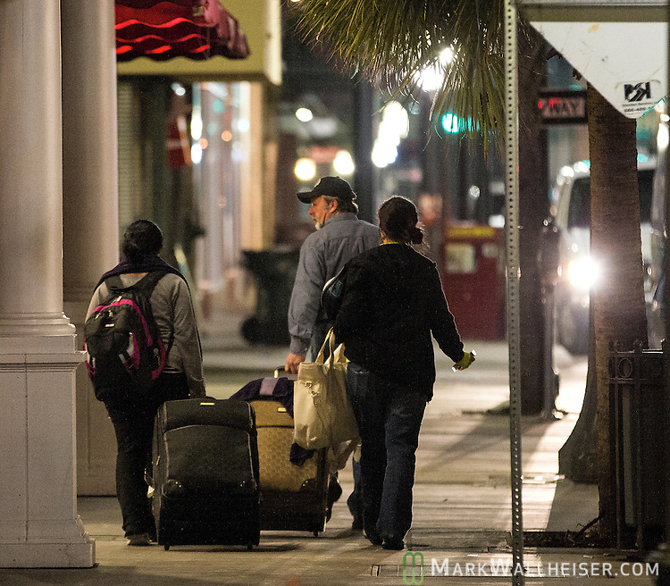 Passengers wonder through downtown looking for a hotel room after they disembarked from the crippled Carnival Triumph cruse ship  after it was towed to port in Mobile, Alabama, USA, 14 February 2013. The 900 foot long (247 meter) ship with 3,143 passengers and a crew of 1,086 lost power after an engine fire on 10 February as it was returning to Galveston, Texas, USA from Cozumel, Mexico. Passengers have reported squalid conditions as sewage systems failed and food supplies dwindled.