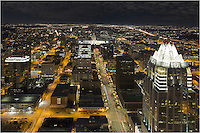 With the UT tower lit orange in the far distance, this image of the the Austin, Texas area looks north from the top of the Austonian, the tallest building in downtown. The main street leading to the Texas capitol is Congress Avenue.