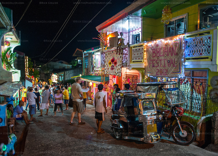 The Buri Bag Project's Mr. Mark Bauer moves methodically down a Sampaloc street packed with homes decorated for the Bulihan Festival's home decorating contest 2012.  The home decorating contest in Sampaloc's Bulihan Festival was held at night this year.  There were over 160 homes competing using a combination of lighting and decorations made from buri or buri products.  Top prize this year was 15,000 Philippine pesos donated by the Buri Bag Project (which is over two months' salary for most Filipino skilled laborers). (Sampaloc, Quezon Province, the Philippines)