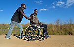 Dominik Tengani gets a push for his wheelchair from his son Donald near their home in Kuwadzana, Zimbabwe. Tengani is vice chair of the Spinal Injuries Association of Zimbabwe, which supports and advocates for the rights of people living with spinal injuries. He says doctors have been unable to diagnose the cause of his medical condition. He uses an appropriately-designed and fitted wheelchair provided by the Jairos Jiri Association with support from CBM-US.