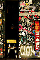 cool graffiti on a door of a barcelona shop with chair in the dorrway, old part of town, base element shop in old barcelona