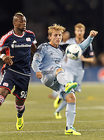Sporting Kansas City defender Seth Sinovic (15) clears the ball as New England Revolution forward Dimitry Imbongo (92) pressures. In the first game of two-game aggregate total goals Major League Soccer (MLS) Eastern Conference Semifinal series, New England Revolution (dark blue) vs Sporting Kansas City (light blue), 2-1, at Gillette Stadium on November 2, 2013.