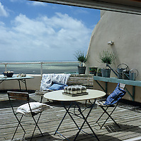 Cushions soften the hard lines of the garden furniture on this teak-decked terrace overlooking the sea