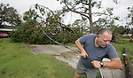 Houma, Louisianna  resident Daniel Trahan pulls power lines bare handed from a downed tree in his yard September 2, 2008 after Hurricane Gustav.    (Mark Wallheiser/TallahasseeStock.com)