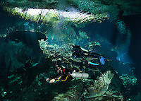 RX0618-D. scuba divers (model released), a professional cave diver equipped with technical gear (note twin sidemount tanks) is acting as a guide on a tour along a marked route through caverns and tunnels accessed by a cenote (the opening above) in the jungle. Riviera Maya, Yucatan Peninsula, Mexico.<br /> Photo Copyright &copy; Brandon Cole. All rights reserved worldwide.  www.brandoncole.com