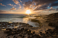 At sunset, large waves crash into the rocky shore of Ka'ena Point State Park, O'ahu.