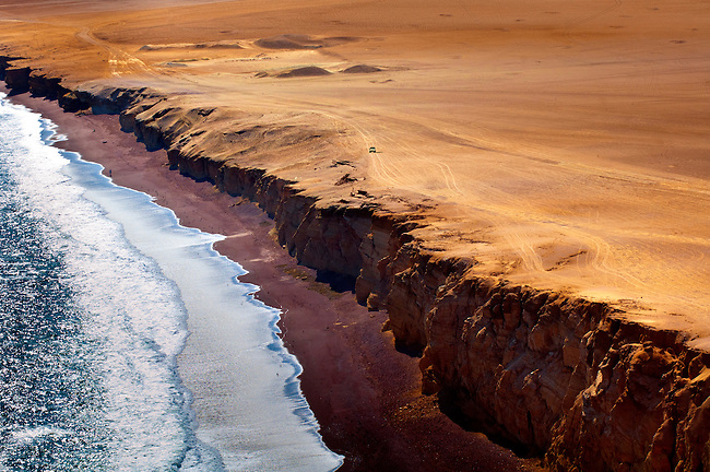 A vehicle follows a dirt trail overlooking the cliffs of Lagunillas Bay in the Paracas National Reserve.  The desert and the Pacific Ocean come together in this national park in Peru.