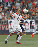 D.C. United midfielder Perry Kitchen (23) traps the ball at midfield. In a Major League Soccer (MLS) match, the New England Revolution (blue) tied D.C. United (white), 0-0, at Gillette Stadium on June 8, 2013.