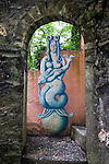 "Portmeirion, in North Wales, is a resort, where no one has ever lived. A self-taught Welsh architect named Sir Clough Williams-Ellis built it out of architectural salvage between the 1920s and 1970s, loosely based on his memories of trips to Portofino. Including a pagoda-shaped Chinoiserie gazebo, some Gothic obelisks, eucalyptus groves, a crenellated castle, a Mediterranean bell tower, a Jacobean town hall, and an Art Deco cylindrical watchtower. He kept improving Portmeirion until his death in 1978, age 94. It faces an estuary where at low tide one can walk across the sands and look out to sea. At high tide, the sea is lapping onto the shores. Every building in the village is either a shop, restaurant, hotel or self-catering accomodation. The village is booked out at high season, with numerous wedding receptions at the weekends. Very popular amongst the English and Welsh holidaymakers. Many who return to the same abode season after season. Hundreds of tourists visit every day, walking around the ornamental gardens, cobblestone paths, and shopping, eating ice-creams, or walking along the woodland and coastal paths, amongst a colourful assortment of hydrangea, rhododendrons, tree ferns and redwoods. The resort boasts two high class hotels, a la carte menus, a swimming pool, a lifesize concrete boat, topiary, pools and wishing wells. The creator describes the resort as ""a home for fallen buildings,"" and its ragged skyline and playful narrow passageways which were meant to provide ""more fun for more people."" It does just that.///Mermaid sculpture relief in an alcove. A motif found all over Portmeirion"