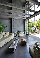 A sitting area in an impressive, industrial style space with exposed grey bricks and beams. A full height paned glass window has a set of doors that lead a garden beyond. The room is furnished in a functional style.