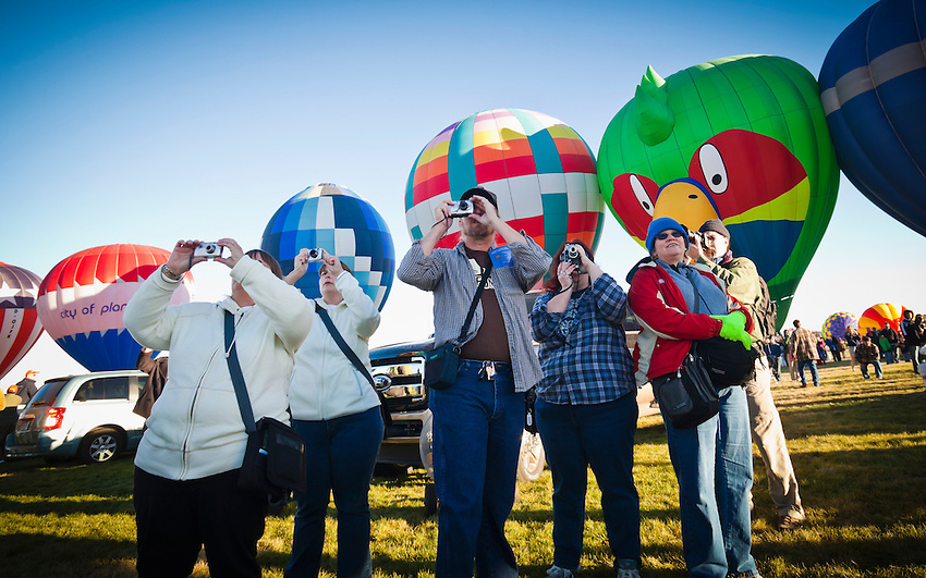 Onlookers at the Albuquerque International Hot Air Balloon Festival take pictures as the balloons take flight.