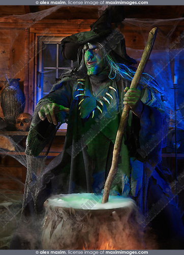 Scary old witch stirring potion in a cauldron inside her cabin on Halloween