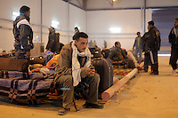 A man text a message on a mobile phone, inside a hall for refugees. Thousands of people, mainly Egyptian workers, fled unrest in Libya and cross the border into Tunisia. Some slept in the open for several days before being processed. .At the same time forces loyal to Col. Gaddafi fought opposition forces in various parts of the country.