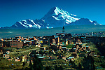 Mt Huayna Potosi rises above houses and a Catholic Church in the city of El Alto, one of the highest major cities in the world, up to 13,615 feet above sea level.  The growing city sits just above La Paz on the Altiplano highlands.