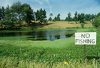 "Disappointing sign saying ""no fishing"" beside a lovely calm rural lake in New England"