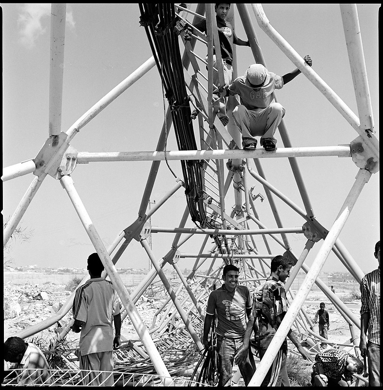 former Morag settlement, Gaza strip, Sept 12 2005.Palestinians from nearby Rafah collect heavy gauge copper wires from the huge radio antennas destroyed by the Israeli army.