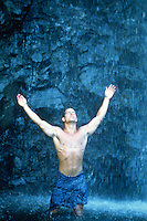 Shirtless man in a sarong with arms up to the sky enjoying a waterwall