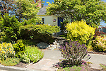 With large shrubs on both sides, front steps lead into a private front yard.