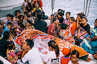 Relatives of a deceased person sit around the coffin on a boat that will take them to one of the outer islands of the atoll where the funeral will occur. Because of overcrowding of Ebeye, all island's cemeteries are full.