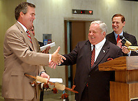 TALLAHASSEE, FL. 8/8/03-Gov. Jeb Bush, left, shakes hands with Senate President Jim King, R-Jacksonville, after King gave him a peace pipe as they announced an agreement on the medical malpractice insurance bill with House Speaker Johnnie Byrd, R-Plant City, Friday at the Capitol in Tallahassee. The proposed bill caps lawsuit damages on pain and suffering awards at an amount higher than Bush wanted. COLIN HACKLEY PHOTO