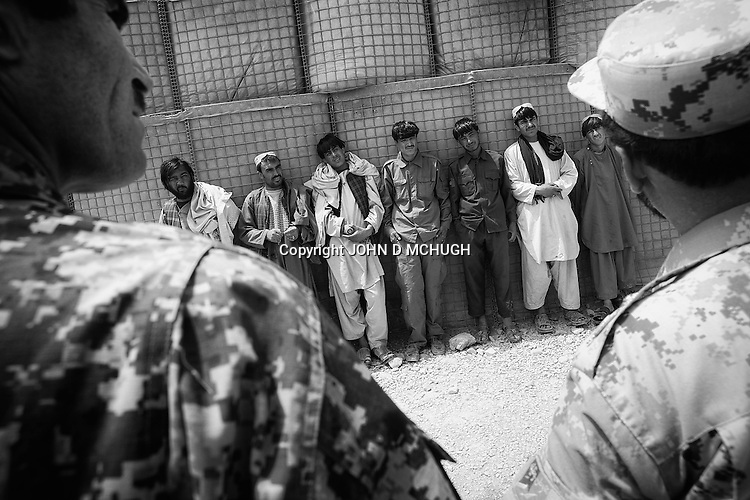 Abdul Jalil, an Afghan Local Police commander, is seen (3L, with prayer beads) alongside other ALP at a meeting with US troops in Panjwayi district, Kandahar, 25 April 2013. Jalil was killed fighting the Taliban days after this photo was taken. (John D McHugh)