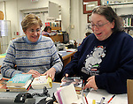 OXFORD, CT. 31 DECEMBER 01_NEW_123108DA01.jpg-Oxford Public Library circulation manager, Kathleen Kycia, left, and library director, Dawn Higginson, right, look over donated books on Wednesday. The Library is planning to reduce the days it is open to conserve on heat and electricity costs.<br />  Darlene Douty