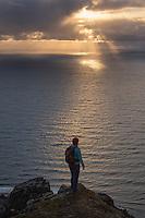 Female hiker watches sun over sea from Nonstind mountain peak, Vestvågøy, Lofoten Islands, Norway