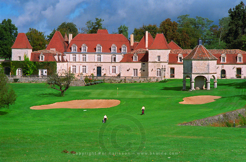 The Chateau des Vigiers in Bergerac near Bordeaux. Luxury hotel and restaurant with a golf course. Two golf players on the fairway to the 18th eighteenth green.  Early 17th seventeenth century. hexagonal dovecote to the right, Bordeaux Gironde Aquitaine France Europe