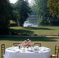 A table is laid for lunch in the sunshine of this summer garden with views down to the river