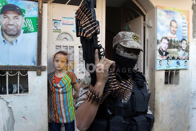 A member of al-Quds brigades, the military wing of Jihad Islamic organisation stands guard during a visit for the home of Hamas militants commander Ahmed Jaabari in Gaza City on November 13, 2013, ahead of the first anniversary an Israeli army operation which was launched after the killing of top Palestinian military commander Ahmed Jaabari in an air strike. The November 2012 fighting between Israel and Palestinian militants in the Gaza Strip lasted one week and costed the lives of at least 136 Palestinians and five Israelis. Photo by Mohammed Asad