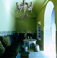 The tiles, sage green walls and banquettes covered in a lush green velvet in this Moroccan home are inspired by a 17th century Dutch oil painting