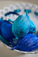 Detail of Easter eggs wrapped in striking blue foil paper in a white ceramic dish
