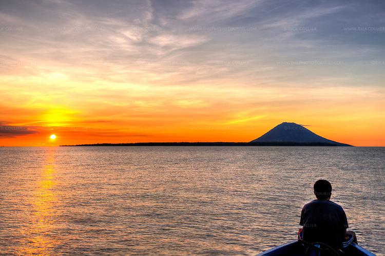 Sunset lights the sky behind Bunaken Island (foreground) and the volcano island Manado Tua beyond.  Bunaken, off North Sulawesi, Indonesia. (HDR image)