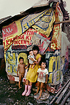 00019_06, PHILIPPINES-10012NF, A mother and her children stand outside their home in Boringot, Manila, Philippines, 1986.<br />