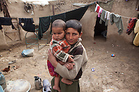 Boy holding young brother in slum housing, Kabul, Afghanistan