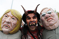 Phoenix, Arizona. April 25, 2012 - Activist actors wear masks in the likeness of Arizona Governor Jan Brewer, the devil, and Maricopa County sheriff Joe Arpaio. The masks were created by renowned Arizona artist Zarco Guerrero (wearing devil's mask). About 500 people protested the controversial law on the same day U.S. Supreme Court justices heard legal arguments on the Arizona vs. United States case. At the end of the march, six activists blocked Central Avenue by sitting in the middle of the street. They all were arrested by the Phoenix Police Department and taken to the Fourth Avenue County Jail. Photo by Eduardo Barraza © 2012