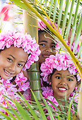 Girls wearing pink plumeria lei and haku head lei pose amid palm trees before a hula performance in Halei'wa, North Shore, O'ahu.