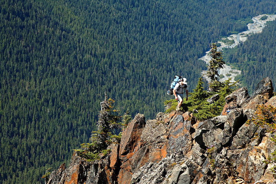 Man high above the Hoh River crossing the rocky spine of The Catwalk dividing High Divide and Bailey Range, Olympic Mountains, Olympic National Park, Washington