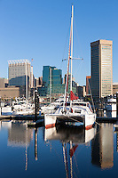 A catamaran waits in its slip for its next journey in front of part of the skyline of Baltimore, Maryland, including the World Trade Center, which is reflected in the waters of the Inner Harbor during the first hour after sunrise.