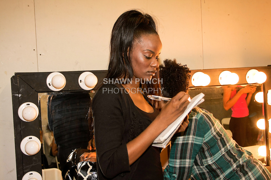 Kevian Lotoya Douglas writes notes backstage during BK Fashion Weekend Spring Summer 2012.