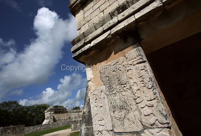 Ball Player in relief at the entrance of the Jaguar Throne with the Southern temple in the distance, Temple of the Jaguars, southern end of the east platform of the court of the Game of Ball, 900-1100 AD, Toltec Architecture, Chichen Itza, Yucatan, Mexico. The temple was also used as the grandstand for the more important spectators. Picture by Manuel Cohen